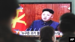 한국 서울역에서 1일 행인들이 김정은 북한 국방위 제1위원장의 신년사 관련 뉴스를 지켜보고 있다.