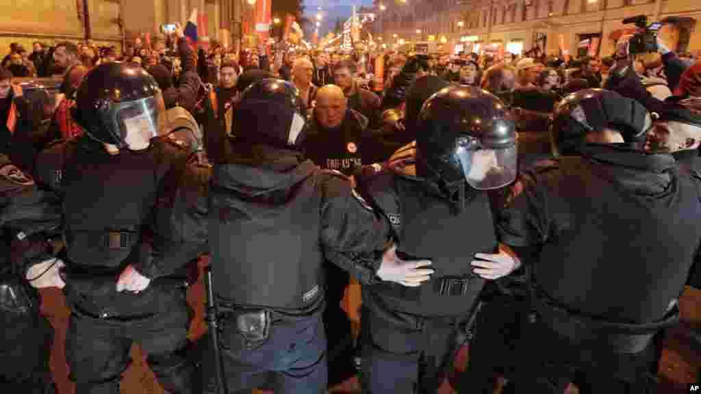 Des policiers anti-émeutes bloquent la voie aux manifestants lors d'un rassemblement à Saint-Pétersbourg, en Russie, le 7 octobre 2017.