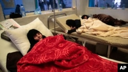 FILE - Women are treated for a suspected cholera infection at a hospital in Sanaa, Yemen, May 15, 2017.