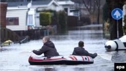 De jeunes garçons rament sur un bateau pneumatique le long d'une rue inondée à Kerkdriel, Pay-Bas,13 Janvier 2011. EPA / WIM Hollemans