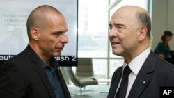 Greek Finance Minister Yanis Varoufakis, left, and Commissioner for Economic and Financial Affairs, Taxation and Customs, Pierre Moscovici at the Informal Meeting of Ministers for Economic and Financial Affairs of the EU in Riga, Apr. 24, 2015.