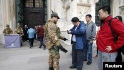 Tentara Italia memeriksa pengunjung di luar gereja Katedral Milan, utara Italia (20/11). Italia dan Swedia meningkatkan pengamanan di wilayah mereka menyusul serangan di Paris minggu lalu.