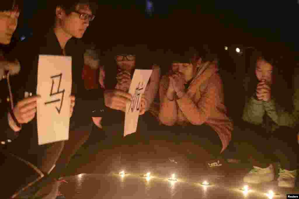 دانشجویان دانشگاهی در یانگژوی چین برای سرنشینان هواپیمای گمشده مالزی شمع روشن کرده و دعا می کنند - ۱۳ مارس ۲۰۱۴