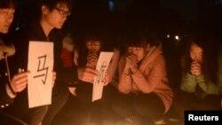 Mahasiswa/i China di Yangzhou, provinsi Jiangsu, memegang kertas dekat lilin-lilin yang menyala sambil berdoa untuk para penumpang Malaysia Airlines penerbangan MH370 yang hilang (13/3).