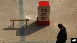 ຊາວບ້ານຄົນນຶ່ງກໍາລັງຢ່າງຜ່ານ ຫີບປ່ອນບັດທີ່ຕັ້ງໄວ້ໃນໂຮງຮຽນ ທີ່ບ້ານ Wukan ເມືອງ Lufeng ແຂວງ Guangdong ພາກໃຕ້ຂອງຈີນ ເມື່ອວັນສຸກ ທີ 2 ເດືອນກຸມພາ, 2012. ຊາວບ້ານພາກັນປະທ້ວງຄັ້ງໃຫຍ່ ຕໍ່ຄວາມບໍ່ທ່ຽງທໍາ ແລະຍຶດດິນຄືນ ພ້ອມທັງຂັບໄລ່ບັນດາເຈົ້າໜ້າທີ່ບ້ານ.