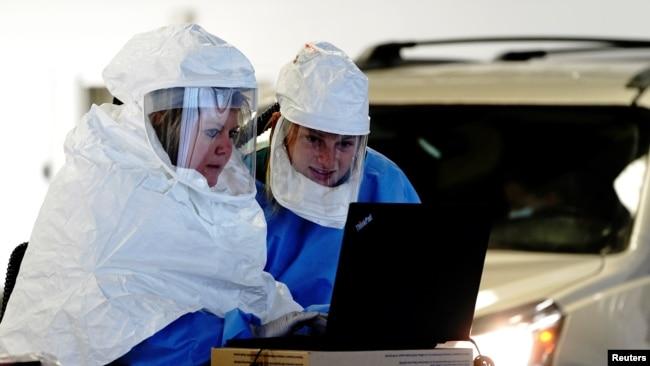 Nhân viên y tế mặc đồ bảo hộ xử lý các mẫu xét nghiệm COVID-19 tại một địa điểm xét nghiệm ngồi trong xe ở Sioux Falls, bang South Dakota, ngày 28 tháng 10, 2020.