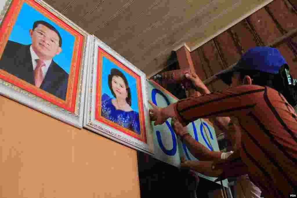 People in Tropeang Lavear display SOS messages next to the photo of Prime Minister Hun Sen and his wife Bun Rany on their wall, Cambodia, November 13, 2014. (Nov Povleakhena/VOA Khmer)