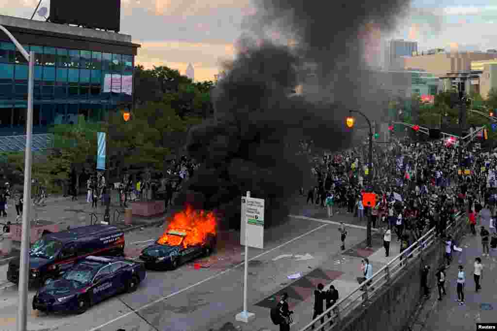 An Atlanta Police car burns as people protest against the death in Minneapolis police custody of African-American man George Floyd, near CNN Center in Atlanta, Georgia, U.S. May 29, 2020. REUTERS/Dustin Chambers TPX IMAGES OF THE DAY