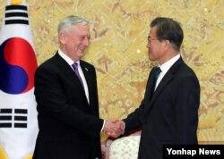한국을 방문한 짐 매티스 미국 국방장관이(왼쪽) 27일 청와대에서 문재인 한국 대통령과 만나 악수하고 있다.