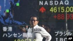 一名男子站在東京的一個電子屏幕前觀看交易情況時的倒影。 (2016年1月15日)