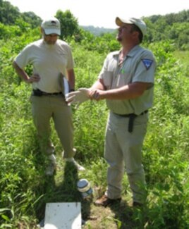 Bob Merz and Dan Koch of the St. Louis Zoo prepare to check a pitfall trap for beetles.