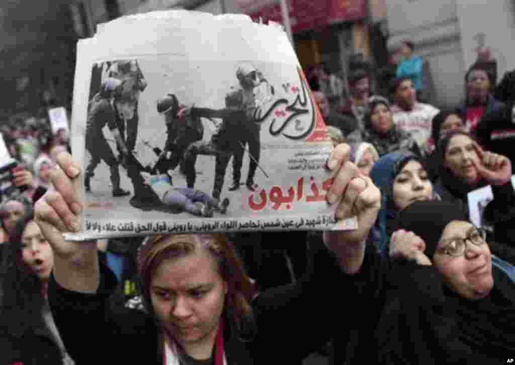 An Egyptian woman raises a copy of Al Tahrir newspaper fronted by a picture showing half naked woman protester beaten by army soldiers as hundreds of Egyptian women march at Cairo streets angered by the recent violence used against them during clashes be