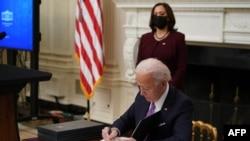 Perezida Joe Biden asinya amategeko ya perezida ku musi wiwe wa mbere ku butegetsi, kw'italiki 21/01/2021.