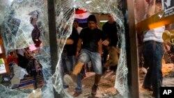 Un hombre da una patada a una ventana rota del edificio del congreso durante los enfrentamientos entre la policía y los manifestantes que se oponen a una enmienda constitucional aprobada que permitiría la elección de un presidente a un segundo mandato, en Asunción, Paraguay, el 31 de marzo de 2017.