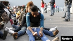 Migrants rest after disembarking from the British assault ship HMS Bulwark at the Sicilian port of Catania after being rescued at sea, Italy, June 8, 2015.