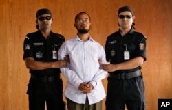 Members of Bangladesh's Rapid Action Battalion (RAB) force escort Farabi Shafiur Rahman, center, a suspect in the murder of an American blogger Avijit Roy, during his presentation to the media in Dhaka, March 2, 2015.