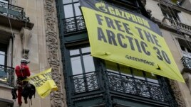 Greenpeace activists install banners in support of their detained colleagues on the front wall of Russia's Gazprom offices in Paris October 9, 2013.
