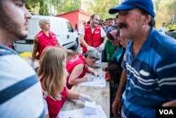 Serbian Red Cross gives food and water to migrants. (A. Tanzeem/VOA)
