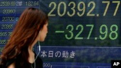 A woman walks past an electronic stock indicator of a securities firm in Tokyo, displaying Tokyo's Nikkei 225 that lost 327.98 points or 1.58 percent to 20,392.77, Wednesday, Aug. 12, 2015.