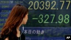 Seorang perempuan berjalan melewati sebuah papan elektronik yang memperlihatkan penurunan indeks Nikkei di Tokyo.
