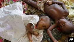 Two children stricken down with malaria rest at the local hospital in the small village of Walikale, Congo.