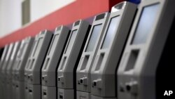 FILE - ATMs, automated teller machines, are lined up during the manufacturing process at Diebold Nixdorf in Greensboro, North Carolina, Aug. 30, 2017.