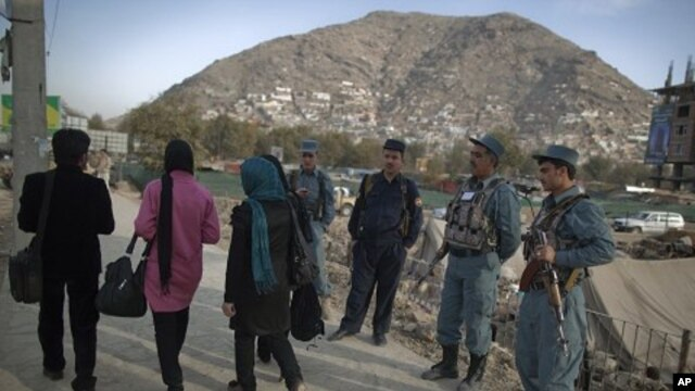 Afghan policemen keep watch near the site where a suicide bomber was killed near the location of the Loya Jirga, or the traditional assembly, in Kabul, November 14, 2011.