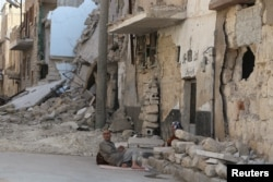 Residents rest on the ground near rubble in a damaged neighbourhood in Aleppo, Syria, July 30, 2015.