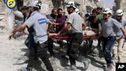 """Syria Civil Defense """"White Helmets"""" rescue people from site of airstrikes, al-Sakhour neighborhood of eastern Aleppo, Syria, Sept. 21, 2016."""