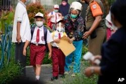 Siswa yang mengenakan masker tiba di hari pertama pembukaan sekolah kembali di Jakarta, Senin, 30 Agustus 2021. (Foto: AP)