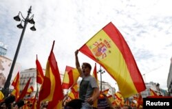 Demonstrators wave Spanish flags during a demonstration in favor of a unified Spain on the day of a banned independence referendum in Catalonia, in Madrid, Spain, Oct. 1, 2017.