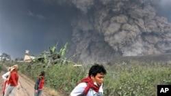 ຊາວບ້ານພາກັນແລ່ນປົບໜີ ຫຼັງຈາກທີ່ພູໄຟ Sinabung ລະເບີດຂຶ້ນຢ່າງແຮງ ຢູ່ Namantaran, ສຸມາດຕາເໜືອ, ວັນທີ 1 ກຸມພາ 2014.