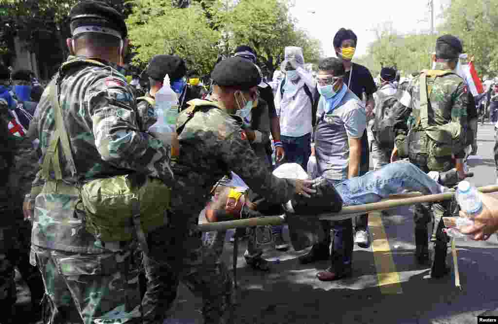 A military medical unit team assists an injured protester after riot police threw a tear gas canister during clashes in Bangkok, Dec. 2, 2013.