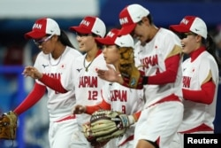 Team Japan shortstop Mana Atsumi (12) celebrates with teammates after an inning ending double play against the United States of America during the sixth inning in the gold medal game of the Tokyo 2020 Olympic Summer Games at Yokohama Baseball Stadium. (Kareem Elgazzar-USA TODAY Sports)