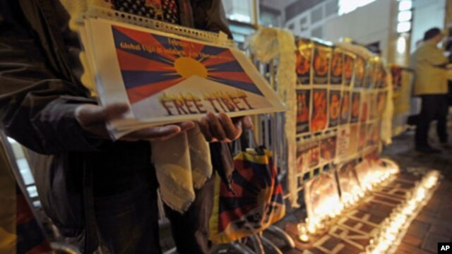 A protester holds a placard next to a Free Tibet candlelit display showing the pictures of Tibetans who died of self-immolation, in front of the Liaison Office of the Central People's Government in the Hong Kong Special Administrative Region, February 22,