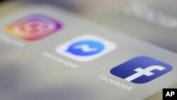 Facebook, Messenger and Instagram apps are displayed on an iPhone, March 13, 2019, in New York. Facebook said it is aware of outages on its platforms including Facebook, Messenger and Instagram.