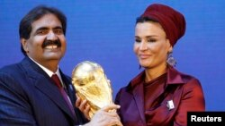 Emir Qatar, Sheikh Hamad bin Khalifa al Thani dan istrinya Sheikha Moza Bint Nasser al-Misnad memegang replika trofi Piala Dunia dari Presiden FIFA Sepp Blatter (unseen) tanda negara itu jadi tuan rumah Piala Dunia 2022. (Foto: Dok)