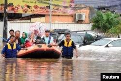 Tim penyelamat mengevakuasi warga yang terkena banjir di Bekasi, Jawa Barat, Rabu (1/1).