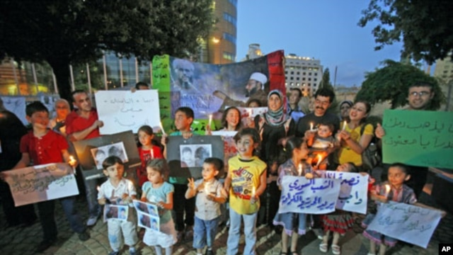 Syrian families and their children carry pictures of 13-year-old Hamza al-Khatib and candles during a protest in front of the United Nations building in Beirut, Lebanon, June 1, 2011