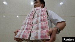 中国山西太原一家银行职员手捧成捆的人民币百元现钞。(资料照片)
