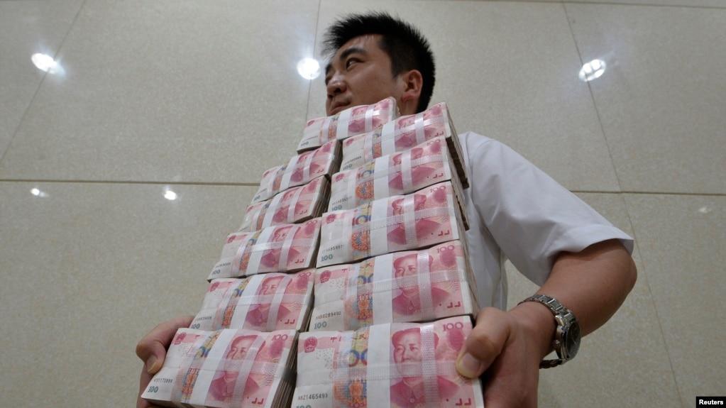 Một nhân viên mang tiền loại 100 nguyên bỏ vào kho ngân hàng tại tỉnh SơnTây, Trung Quốc (ảnh chụp ngày 4/7/2013)