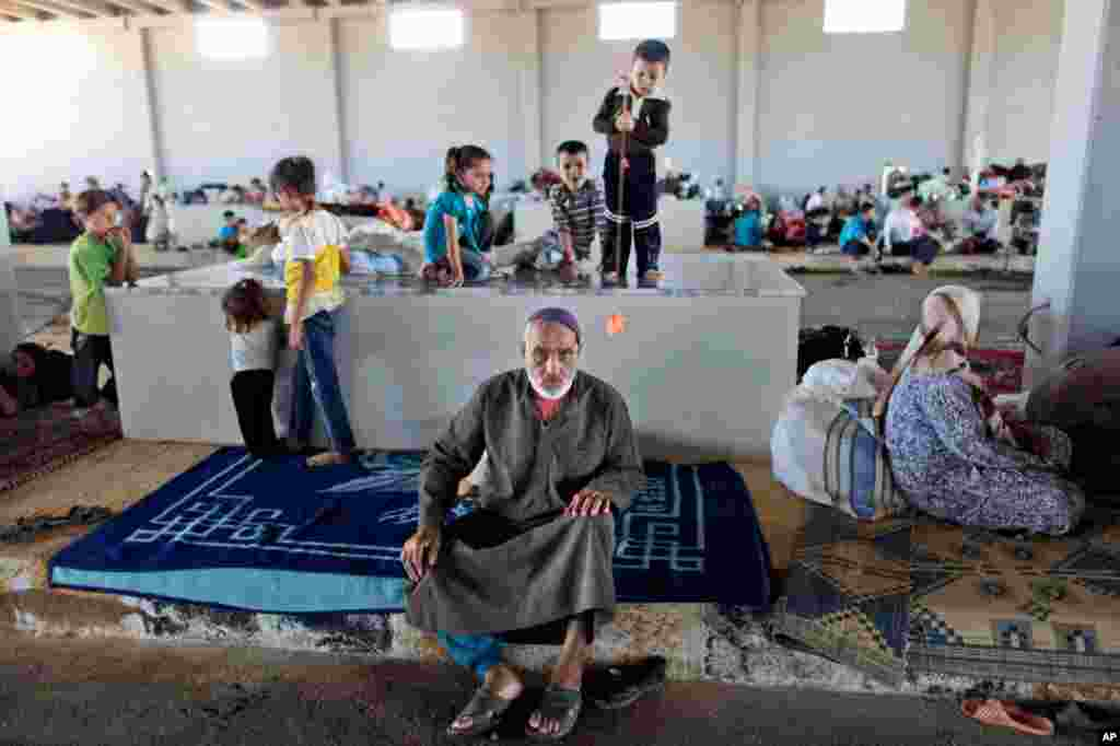 A Syrian man takes refuge at the Bab Al-Salameh border crossing in Azaz, August 23, 2012. Thousands of Syrians who have been displaced are struggling to find safe shelter while shelling and airstrikes continue.