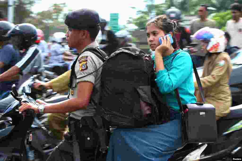 A police evacuates his wife in a motorcycle in Banda Aceh. (Reuters)