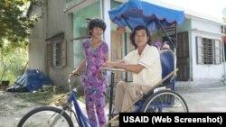 Một người khuyết tật tại Quảng Nam ngồi trên chiếc xe lăn 3 bánh được cấp từ dự án hỗ trợ của USAID. Photo USAID.