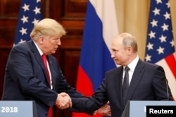 FILE - U.S. President Donald Trump and Russian President Vladimir Putin shake hands as they hold a joint news conference after their meeting in Helsinki, July 16, 2018.