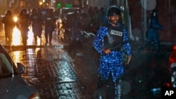 A Maldivian policeman charges with a baton towards protesters after the government declared a state of emergency, in Male, Maldives, Feb. 6, 2018.