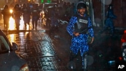 A Maldives policeman charges with a baton towards protesters after the government declared a state of emergency, in Male, Maldives, early Tuesday, Feb. 6, 2018.