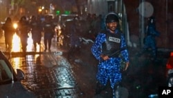A Maldives policeman charges with baton towards protesters after the government declared a 15-day state of emergency in Male, Maldives, early Tuesday, Feb. 6, 2018.