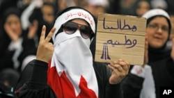 """一名巴林什叶派妇女举着的标语牌上写道""""我们的要求是为了国家利益"""""""
