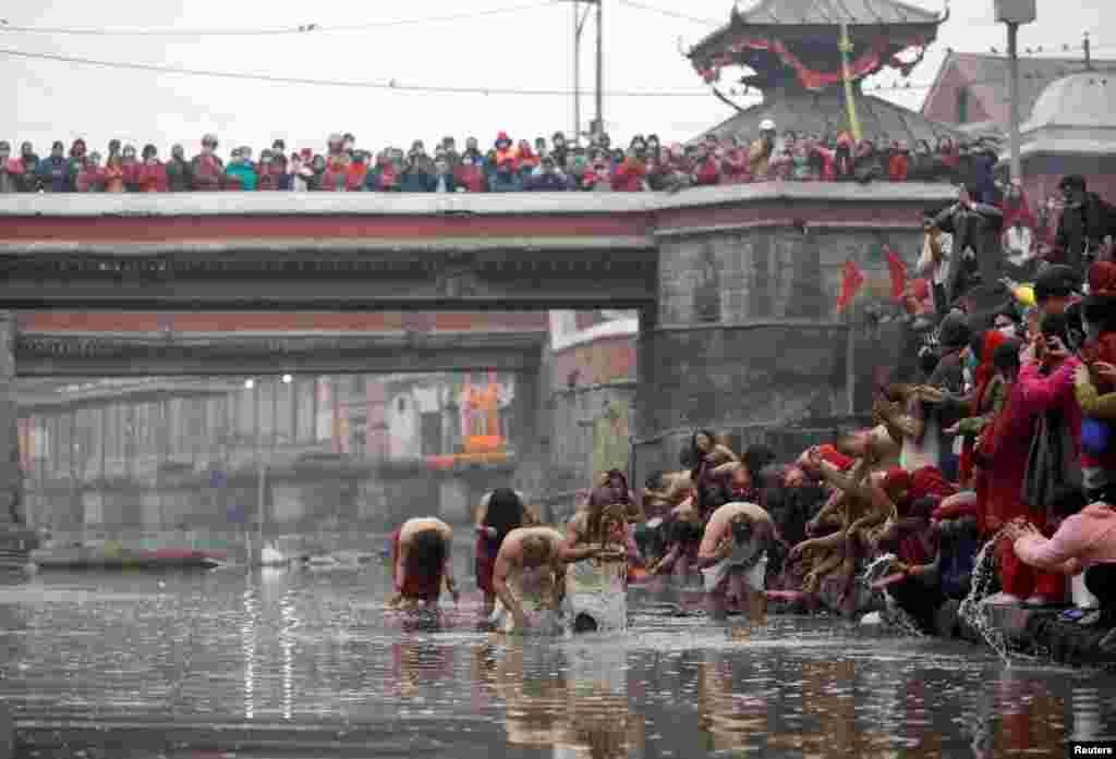 Devotees take a holy bath at Bagmati River in Pashupatinath Temple during the Swasthani Brata Katha festival in Kathmandu, Nepal.